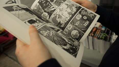 person holding open comic book