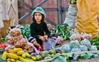 child selling vegetables at market