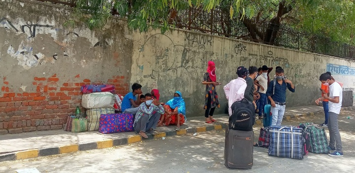 Stranded migrant workers during fourth phase of the lockdown because of COVID-19 pandemic in Delhi, taking rest on the way to their village near New Delhi railway station