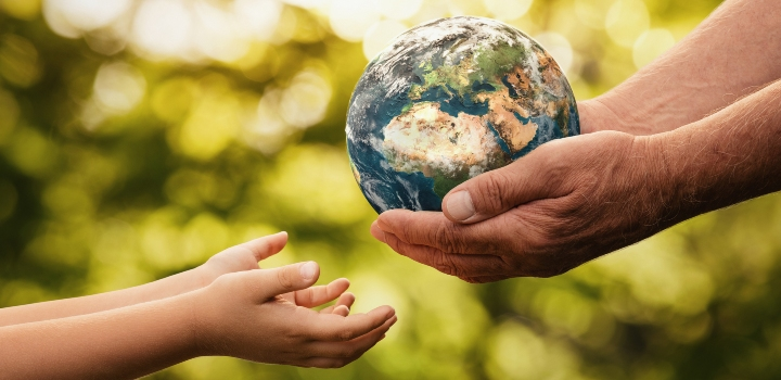 Senior hands giving small planet earth model to a child