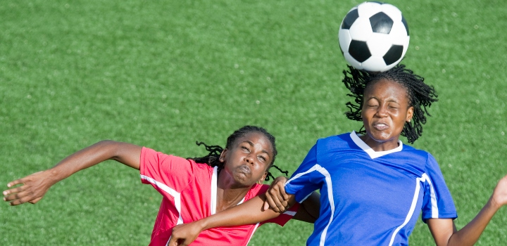 Female footballer heading football