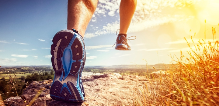 Trail runner, view of training shoes, landscape and bright sun