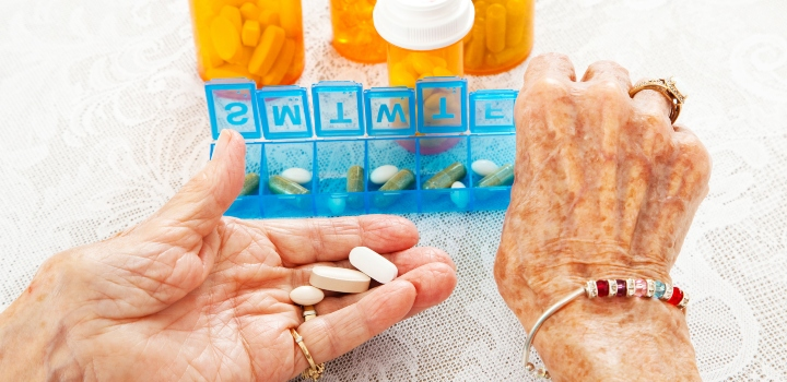 Elderly woman's hands sorting pills into a pill organiser