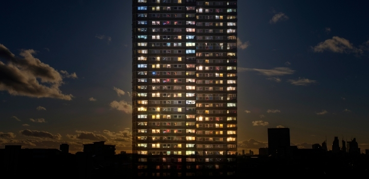 Tower block with many lights on against backdrop of city buildings and early night sky