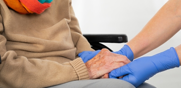 Care home worker wearing PPE holding seated elderly woman's hands