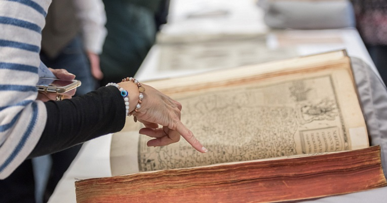 Hand pointing at medieval manuscript